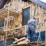 Construction worker thermally insulating house facade with glass wool.