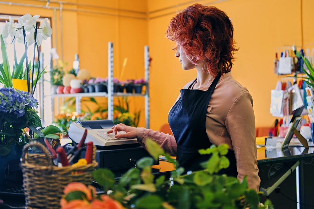 Female flower seller using cash register in a market shop.